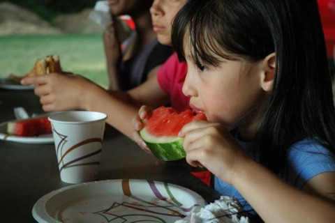 Kids eat watermelon at a neighborhood gathering