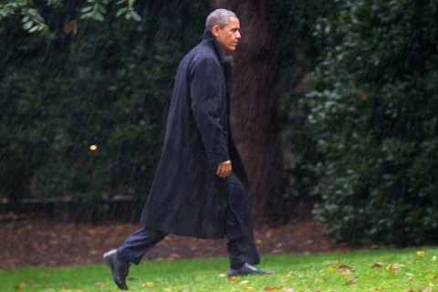 President Barack Obama walks toward the White House in a driving rain