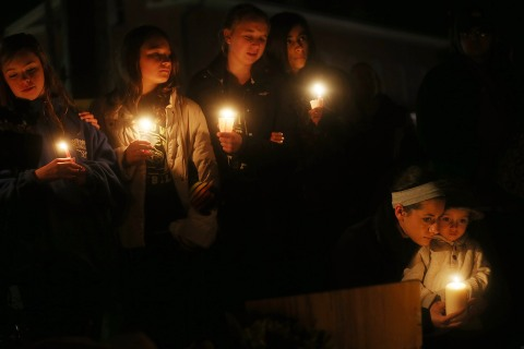 image: mourners hold candles at a memorial for victims on the first Sunday following the mass shooting at Sandy Hook Elementary