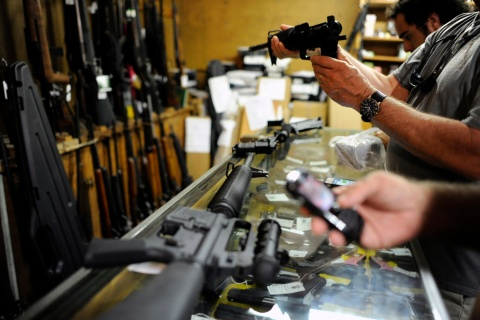 Customers look over the last two AR-15 style rifles for sale inside the Bullet Hole gun shop in Sarasota