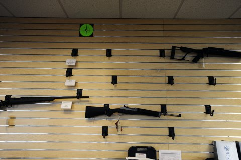 image: Rifles hang on a near empty display wall at Centennial Gun Store in Centennial, Colo., Dec. 20, 2012.