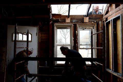 image: Peter Gill, center, works with his father James, left, and friend Mark Faljean on making repairs to his home that was damaged by flood waters during Hurricane Sandy in the New Dorp neighborhood of Staten Island, New York, Jan. 15, 2013.
