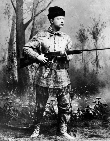 A full-length studio portrait of Former President Theodore Roosevelt wearing hunting gear and holding a Winchester gun in an artificial forest setting, circa 1900.