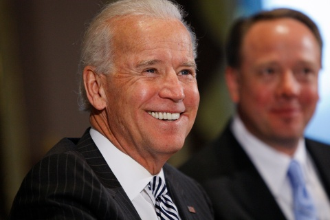 Biden smiles as he sits down to a meeting with representatives from the video game industry, in a dialogue about gun violence, in his office in Washington