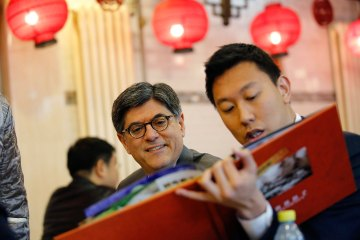 U.S. Treasury Secretary Lew chooses dishes from a menu as he lunches with U.S. government officials at a dumpling restaurant in Beijing