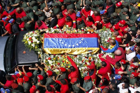 A vehicle carries the coffin with the remains of late Venezuelan President Hugo Chavez is accompanied by thousands of mourners during a parade through the streets of Caracas to the Military Academy in Caracas