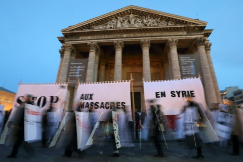 """Protesters march past banners that read """"Stop massacres in Syria"""" in front of the Pantheon in Paris"""