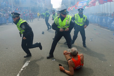 Police officers draw their weapons after hearing a second explosion near the finish line of the 117th Boston Marathon in Boston, on April 15, 2013.
