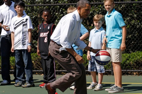 U.S. President Obama dribbles the ball past some children while doing some basketball drills during the annual Easter Egg Roll at the White House