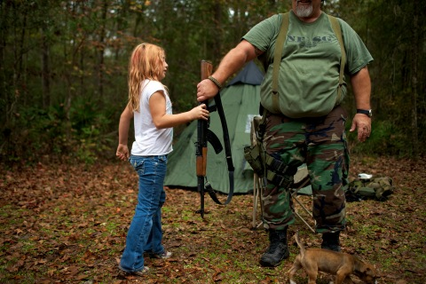 Brianna, 9, of the North Florida Survival Group hands an AK-47 rifle to leader Jim Foster before heading out to conduct enemy contact drills during a field training exercise in Old Town