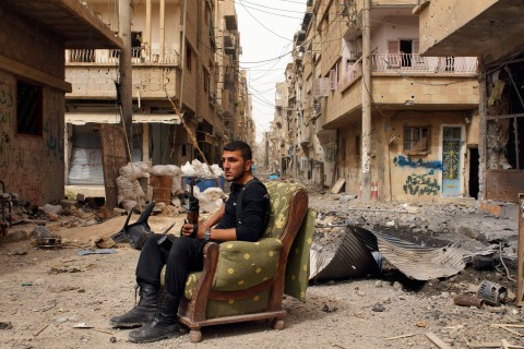 Member of the Free Syrian Army holds his weapon as he sits on a sofa in the middle of a street in Deir al-Zor
