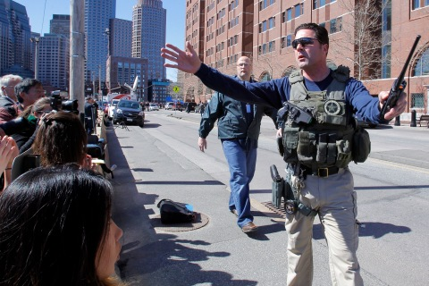 A U.S. marshal gestures to a crowd of journalists and people who were evacuated from the John Joseph Moakley United States Courthouse back during a bomb threat in Boston