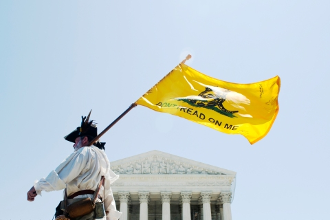 Tea party activist William Temple marches in front of the U.S. Supreme Court, June 27, 2012.