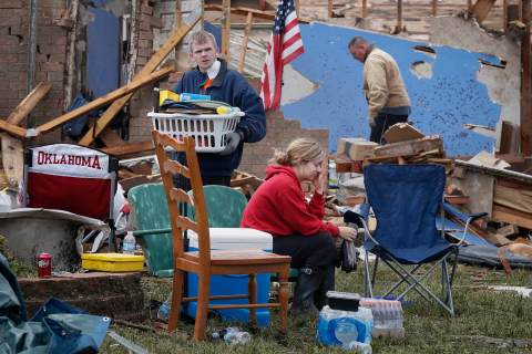 Resident Taylor Tennyson sits in the front yard as family members salvage the remains from their home which was left devastated by a tornado in Moore, Okla., on May 21, 2013.