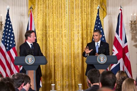 British Prime Minister David Cameron listens as President Barack Obama speaks during their joint news conference in the East Room of the White House.