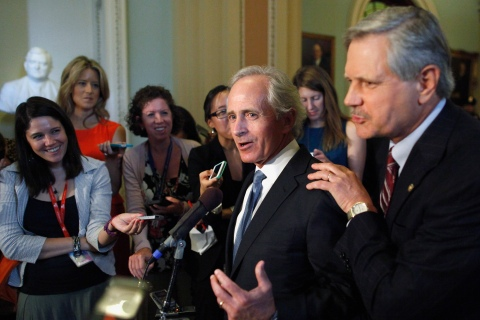 U.S. Senator Corker jokes with Senator Hoeven as they talk about amendment to immigration legislation in Washington