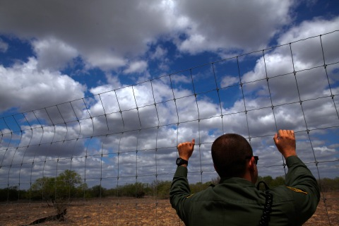 A U.S. Border Patrol agent looks out at the desert near Falfurrias, Texas, on March 29, 2013.