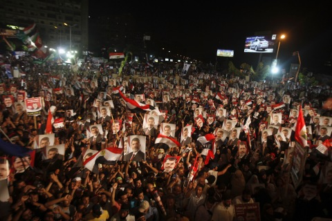 Supporters of Egypt's President Mohamed Mursi, holding his picture, react after the Egyptian army's statement was read out on state TV, at the Raba El-Adwyia mosque square in Cairo