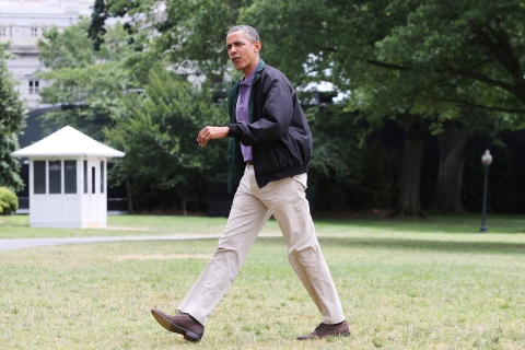 Obama walks across the South Lawn as he returns via Marine One helicopter from a weekend visit at Camp David to the White House in Washington