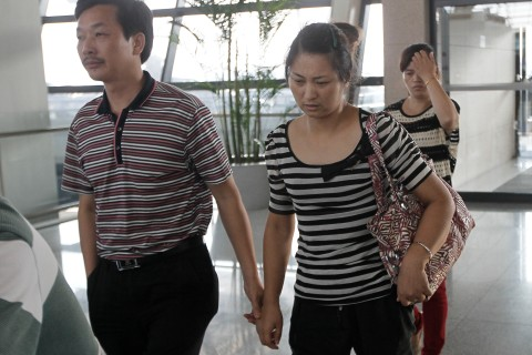 The parents of Wang Linjia, one of the two girls killed during the Asiana Airlines plane crash on Saturday, leave for San Francisco from Shanghai Pudong airport