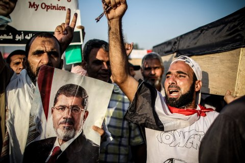 Morsi supporters chant for justice as they carry symbolic coffins of the victims of the Rabaa massacre in Cairo on July 30, 2013.