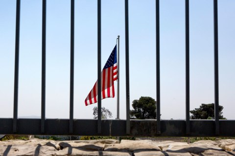 A United States flag flies behind a tall fence at the United States Consulate General building in Jerusalem, Israel, 03 Aug. 2013.