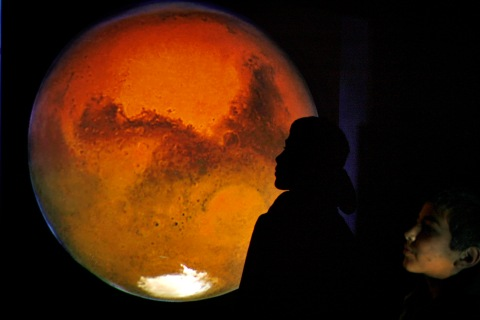 A boy poses with a projection of Mars