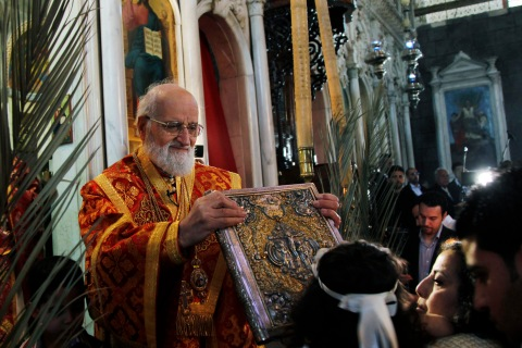 Patriarch Gregorios III Laham of Antioch and All the East holds a Bible for a child to kiss during the Palm Sunday mass at al-Zitoun church in Damascus