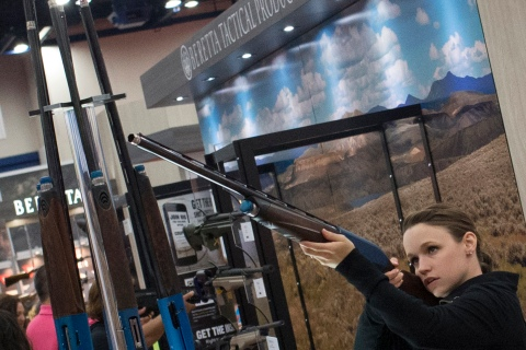 A woman takes aim with a Beretta shotgun at an exhibit booth at the George R. Brown convention center, the site for the National Rifle Association's (NRA) annual meeting in Houston, Texas