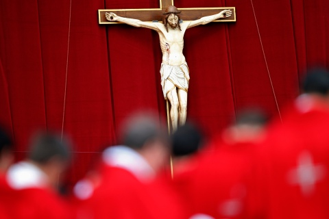 Priests stand in front of a crucifix as Pope Francis leads a mass in Saint Peter's Square at the Vatican