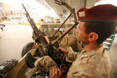 An army trooper sits beside a machinegun that is mounted on a patrol vehicle at at checkpoint in Sanaa