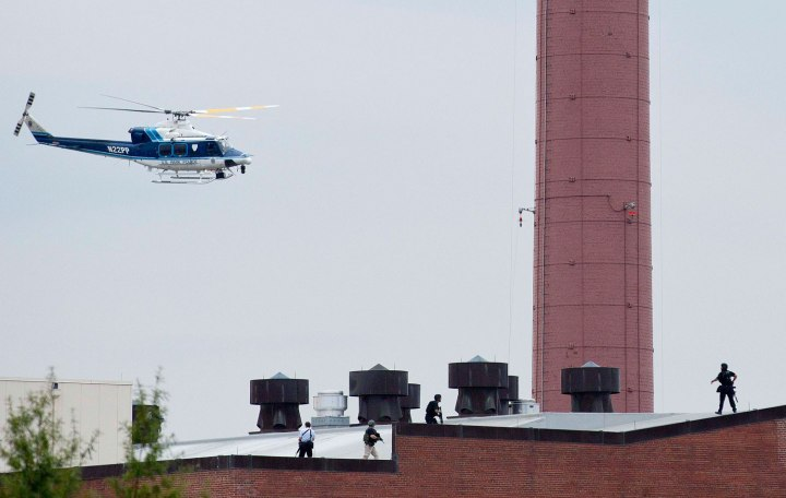 A police helicopter hovers as police walk on the roof of a building as they respond to a shooting at the Washington Navy Yard, in Washington, D.C., on Sept. 16, 2013.