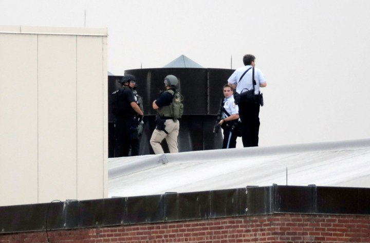 Law enforcement officers are deployed on a rooftop as they respond to a shooting on the base at the Navy Yard in Washington, D.C., on Sept. 16, 2013.