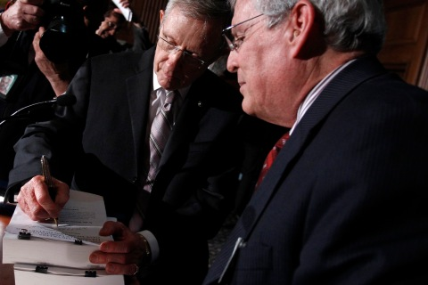 U.S. Senate Majority leader Reid signs a copy of the bill for Pollack after the Senate approved a package of changes to President Obama's landmark healthcare overhaul in Washington
