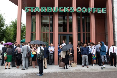 People stand outside a Starbucks Coffee shop that has been closed as police respond to a shooting at the Washington Navy Yard in Washington