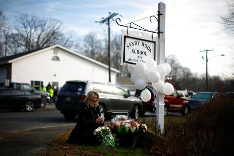 A woman places flowers at a memorial near a sign for Sandy Hook Elementary School