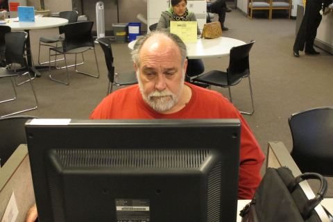 In this hursday Dec. 26, 2013 file photo,  Richard Mattos, 59, looks for jobs at a state-run employment center in Salem, Ore.
