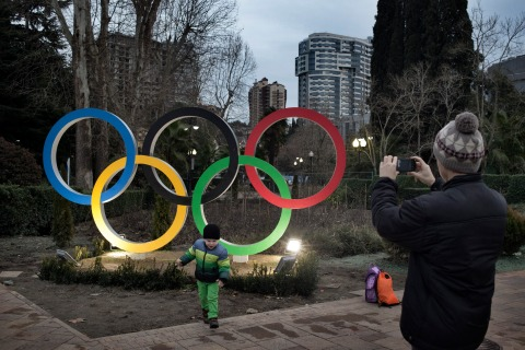 A child plays near an Olympics logo in Sochi, Russia, Jan. 16, 2014.