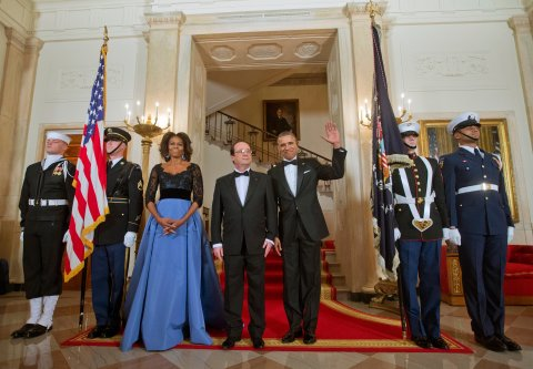 First Lady Michelle Obama and President Barack Obama with French President Francois Hollande, center, pose at the Grand Staircase as they arrive for a State Dinner, Tuesday, Feb. 11, 2014, at the White House in Washington.