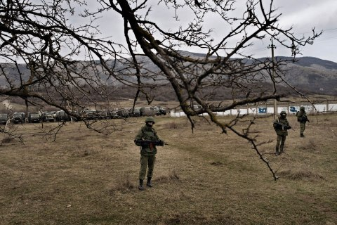 Troops stand guard near the base in Perevalnoye on Sunday. Hundreds of soldiers in unmarked uniforms surrounded the base, using vehicles with Russian license plates.